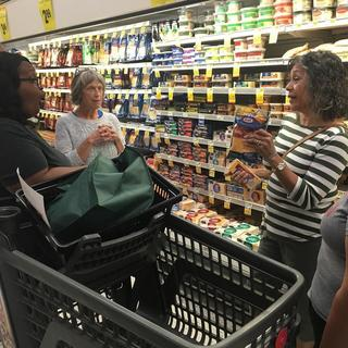 Three women in the cheese aisle at a grocery store.
