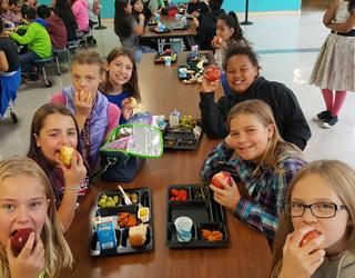 A group of seven elementary students smile while they eat apples and their school lunch in the cafeteria.