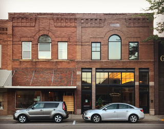 "Two cars parked in front of a row of brick storefronts, one has a sign reading ""Granite Falls Bank"".  """