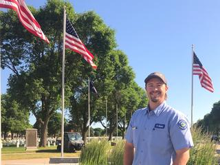 Trevor Blake at Fort Snelling National Cemetery with flags waving