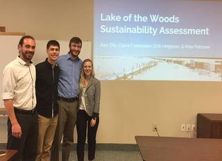Four students standing next to a presentation slide showing on the wall. Lake of the Woods Sustainability Assessment.