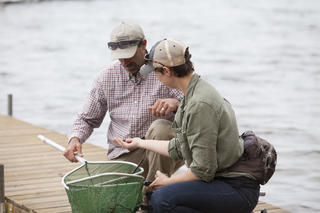 two people on a dock looking at something they found in fishing nets