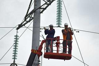 Workers fixing an electrical power line.