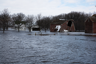 Flooded farm with damaged barn.