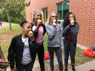 A group of four students eat an apple outside of their school building.