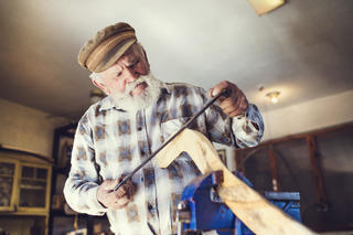 A senior woodworker working in their shop
