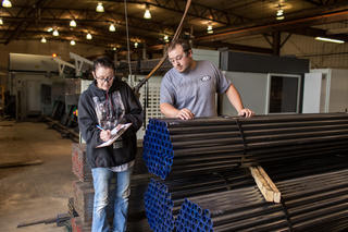 Twp employees working at a manufacturing pipe facility