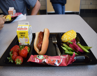A school lunch tray with a meal that includes a hotdog, corn on the cob, snap peas, fresh strawberries and lowfat milk.