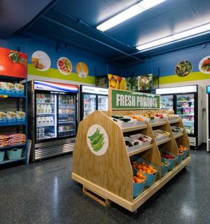 A supershelf food shelf looks like a grocery store displaying fresh produce in bins, and fresh food in cold storage. Paintings of fruits and vegetables are on the walls.
