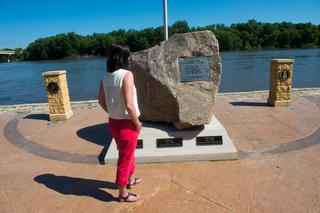 Tourist looking at a memorial plaque on a river