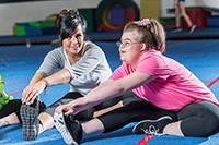 Downs syndrome woman doing exercise with instructor